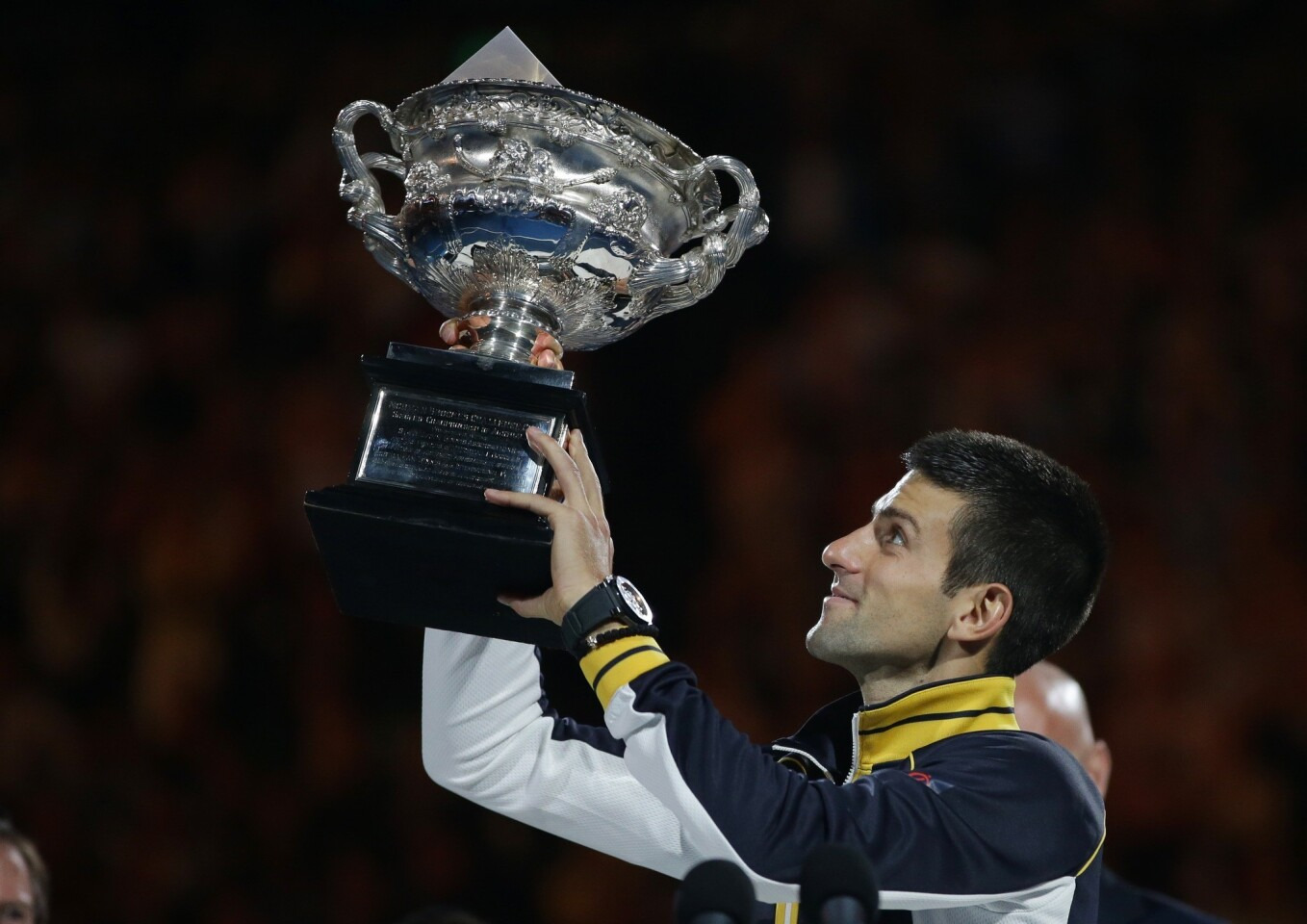 Novak Djokovic becomes the first player in the Open era to hold aloft the Australian Open trophy for the third consecutive year.