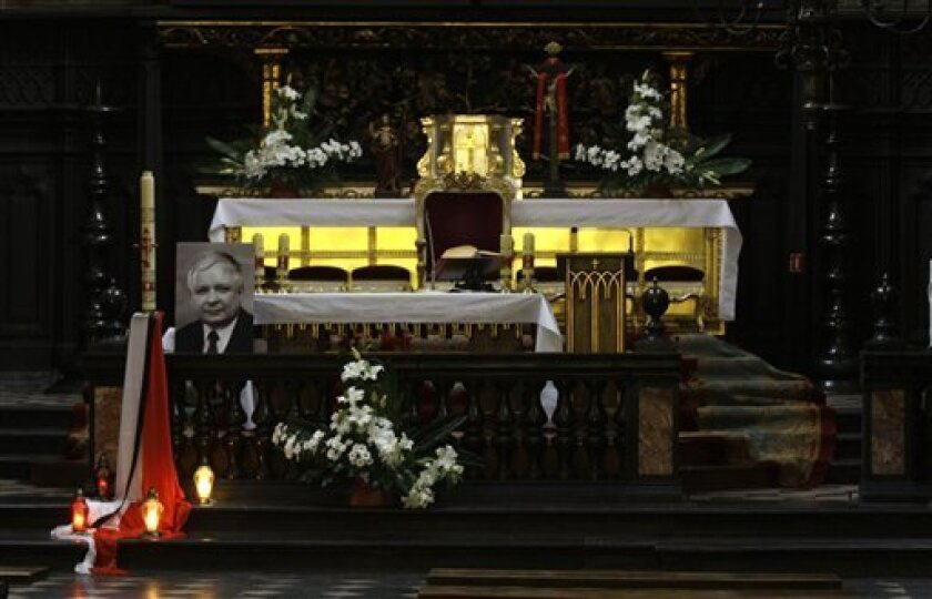 A photo  of a late Polish President Lech Kaczynski is placed  at an altar inside the Mariacki church in Krakow, Poland Friday, April 16, 2010. Polish President Lech Kaczynski and his wife, Maria Kaczynska who was killed in a plane crash in Russia are to be buried Sunday April 18, 2010 after a state