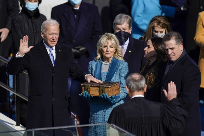 Joe Biden has a hand raised and his other on a Bible held by Jill Biden. Chief Justice John G. Roberts Jr. has a hand raised.