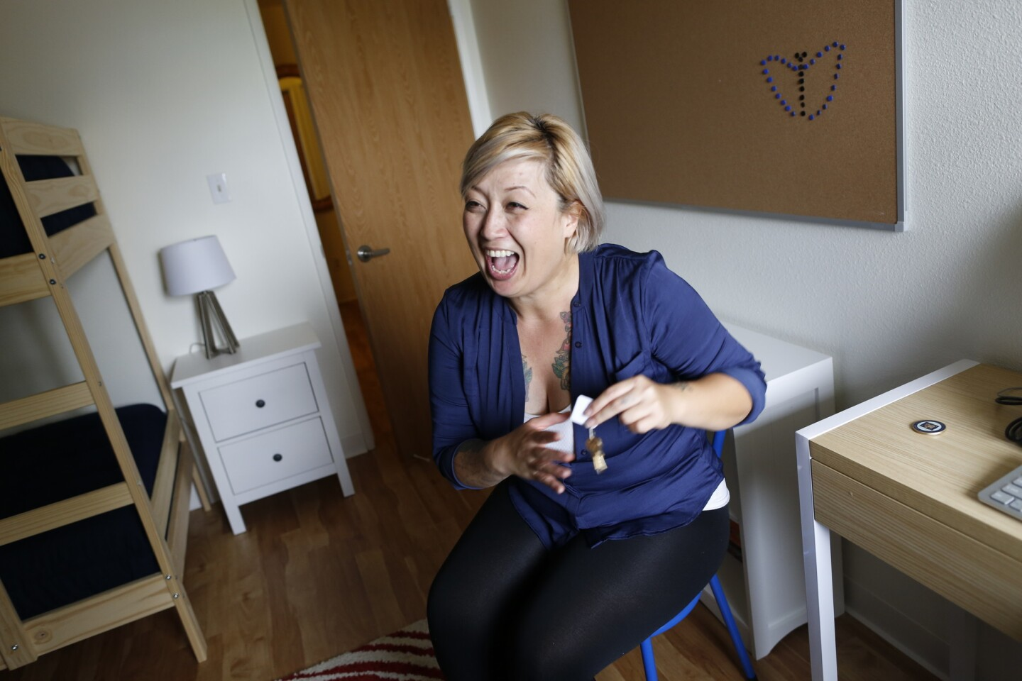 With a beaming smile on her face, Navy Veteran Maria Teresa Alcazar, shakes the keys to her new home as she sits in her son's bedroom, the day she officially received the keys.