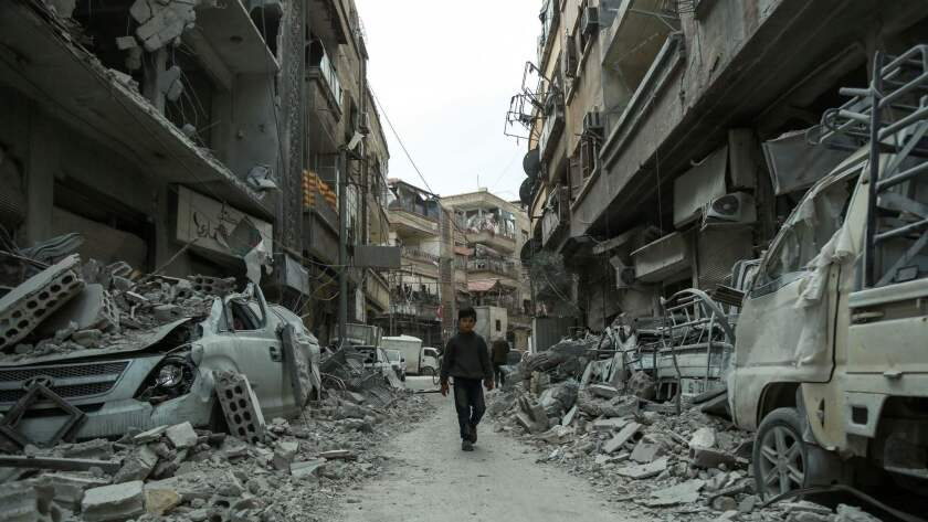 A Syrian child walking down a street past rubble from destroyed buildings, in the rebel-held town of Douma