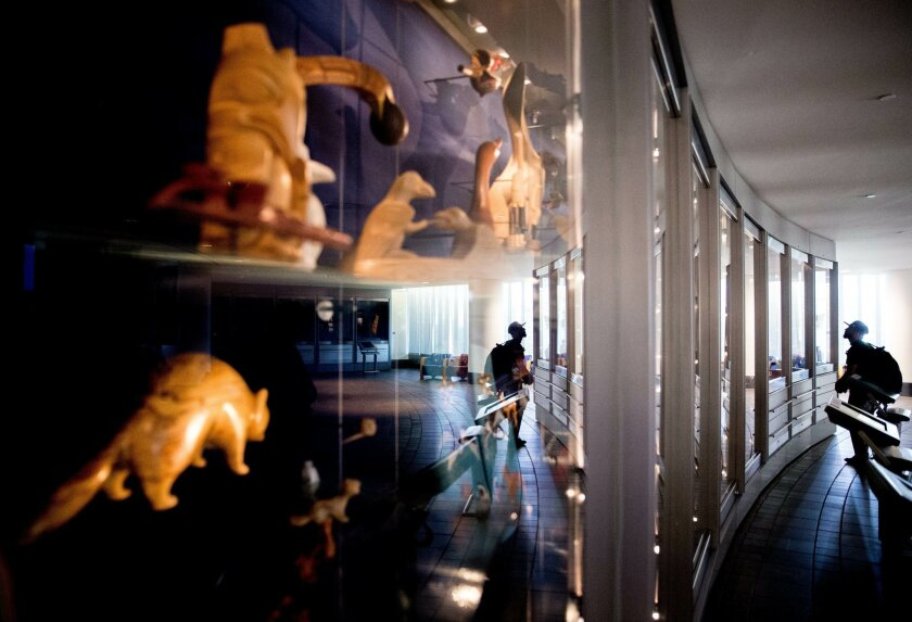 FILE - In this Tuesday, May 24, 2016 file photo, a man looks at Native American artifacts as a group of American Indian advocates hold a news conference nearby at the Smithsonian National Musem of the American Indian, in Washington, to contest a Paris auction house's upcoming auction of Native Amer