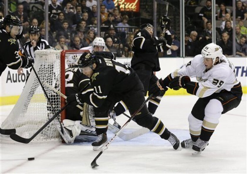 Dallas Stars center Derek Roy (11) helps clear away the puck as Anaheim Ducks' Matt Beleskey (39) pressures on the play in the second period of an NHL hockey game on Thursday, March 14, 2013, in Dallas. (AP Photo/Tony Gutierrez)