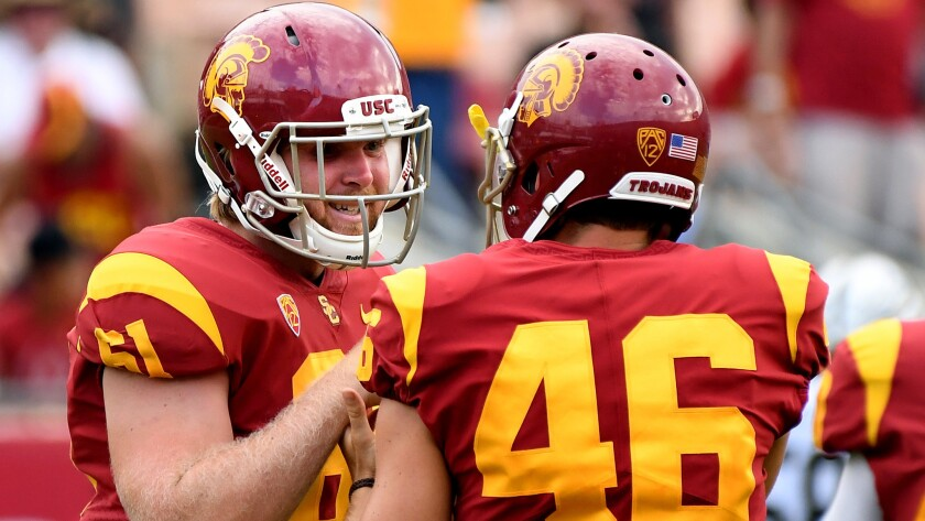 Jake Olson is congratulated by USC teammate Wyatt Schmidt (46) after snapping the ball for an extra point against Western Michigan during the fourth quarter Saturday.