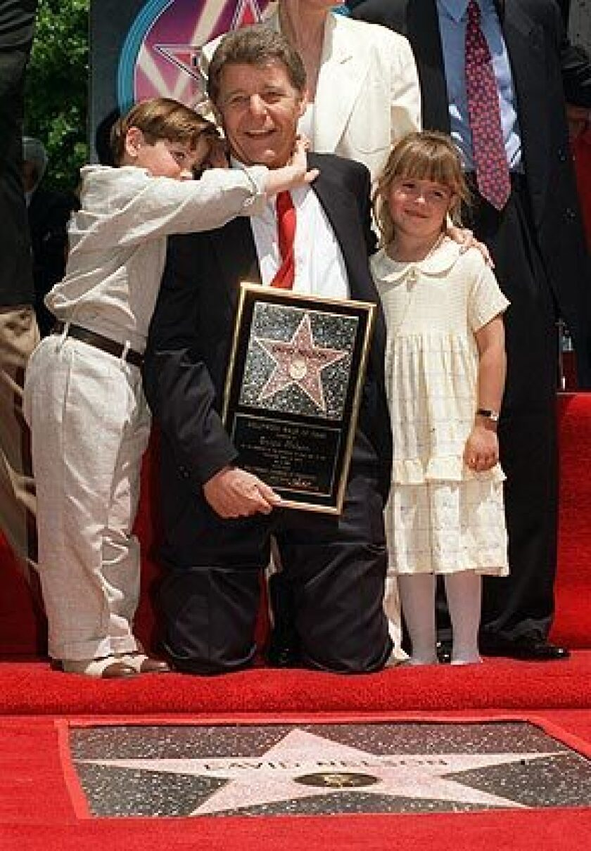 """Actor David Nelson poses with his grandson, Michael Woolery, and family friend Ashley Holt as he is honored with the 2,065th star on the Hollywood Walk of Fame on May 9, 1996. Nelson, who starred on his parents' popular television show, """"The Adventures of Ozzie and Harriet, """" died in Los Angeles on Tuesday. He was 74. See full story"""