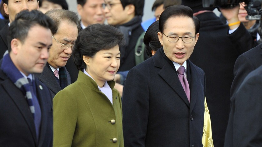 South Korea's Park Geun-hye walks with outgoing President Lee Myung-bak, right, during her presidential inauguration ceremony at the National Assembly in Seoul on Feb. 25, 2013.