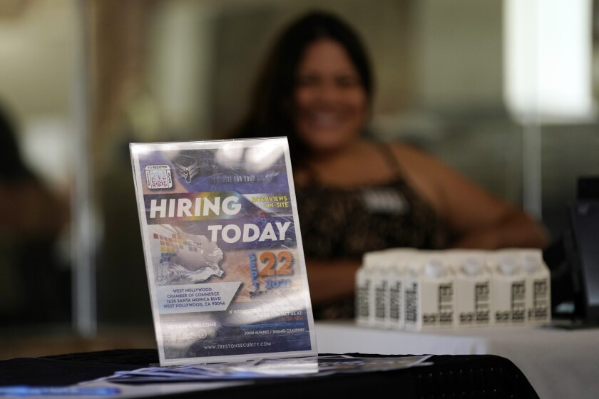 A hiring sign is placed at a booth for prospective employers during a job fair Wednesday, Sept. 22, 2021, in the West Hollywood section of Los Angeles. The number of Americans applying for unemployment aid rose last week for a second straight week to 351,000, a sign that the delta variant of the coronavirus may be disrupting the job market's recovery, at least temporarily.(AP Photo/Marcio Jose Sanchez)