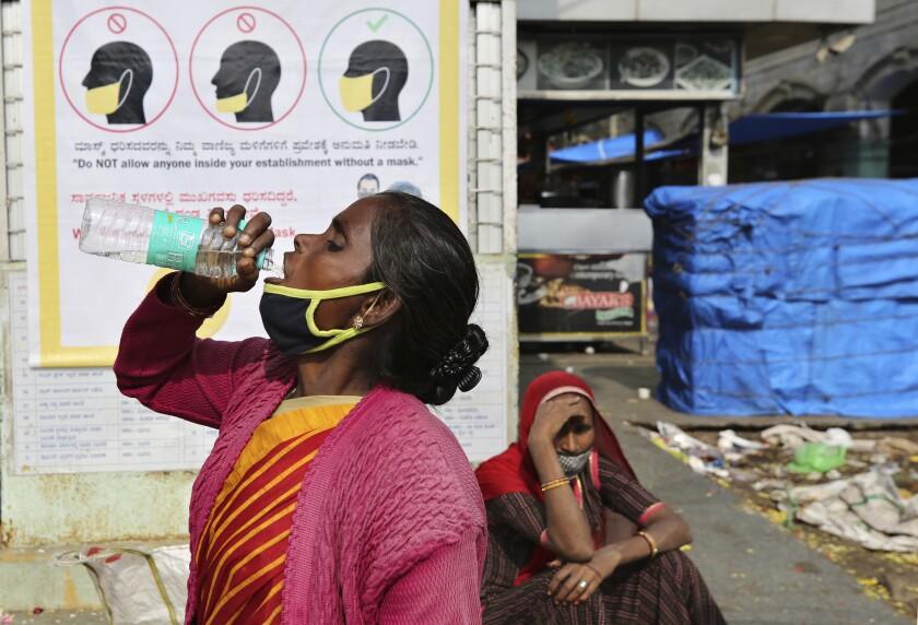 Una mujer india se baja la mascarilla para beber cerca de un cartel que explica el uso correcto de la mascarilla en un mercado en Bengaluru, India, el 29 de octubre de 2020. (AP Foto/Aijaz Rahi)