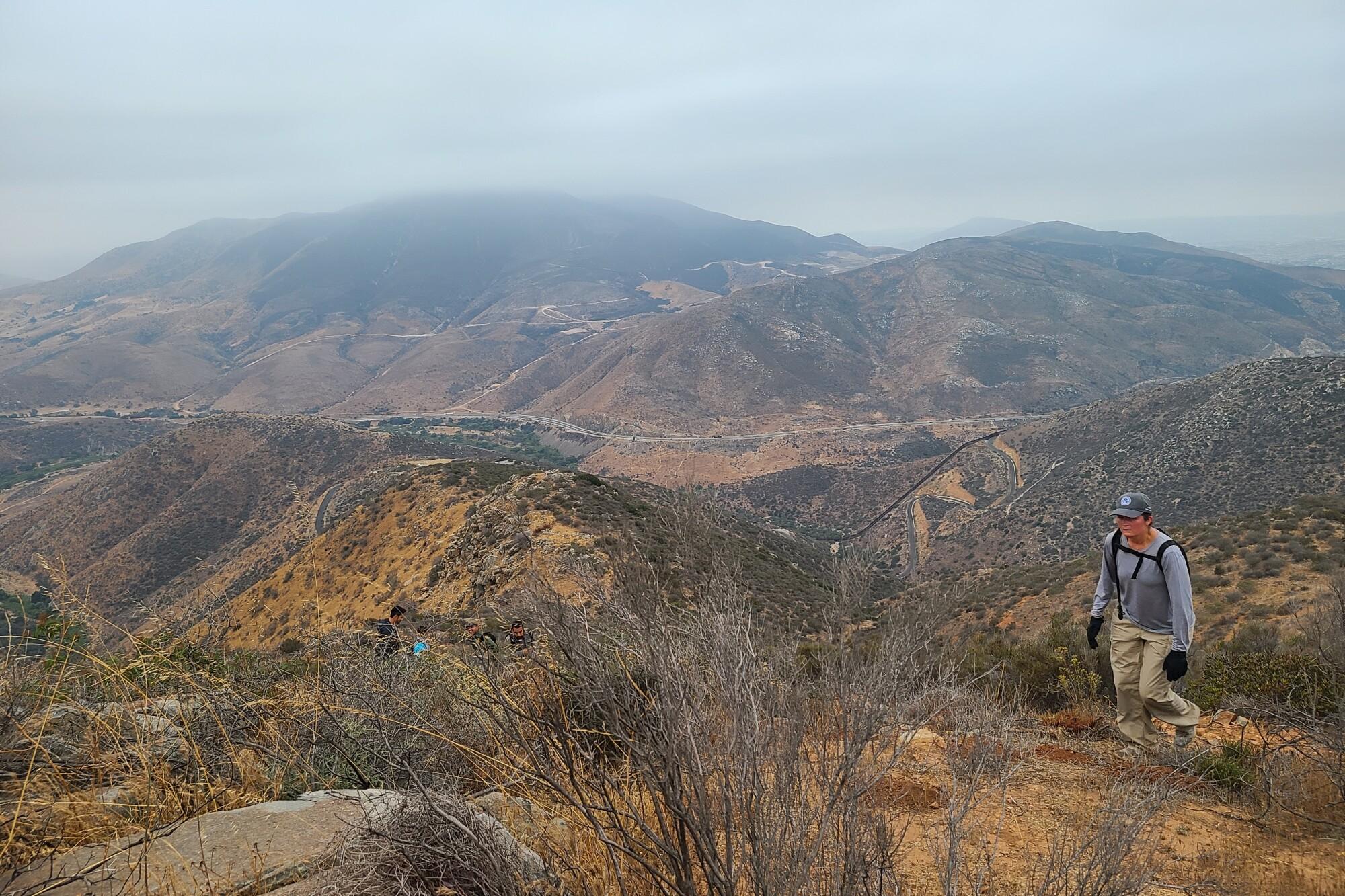 La portavoz de Aduanas y Protección de Fronteras, Jacqueline Wasiluk, sube una empinada pendiente en la montaña de Otay