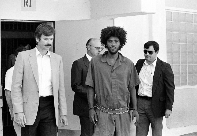 Kevin Cooper, center, shortly after his arrest in the slashing deaths of four people in Chino Hills.