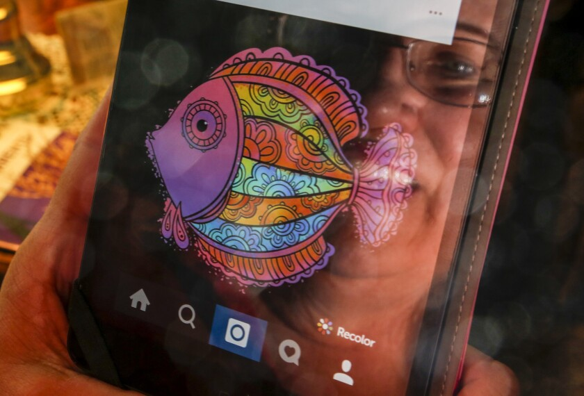 At home in Long Beach, Cheri Brown is reflected on the screen of her iPad Mini where she makes vibrant graphic designs using the coloring app Recolor.