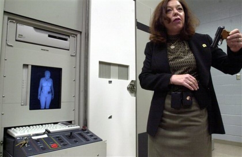 """FILE - In this June 25, 2003 file photo, Susan Hallowell holds up a side arm that was detected by the """"backscatter"""" machine at the Transportation Security Administration in Egg Harbor Township, N.J. Stifel Nicolaus analyst David Schick said Monday, Dec. 28, 2009, whole-body imagery systems _ rather"""