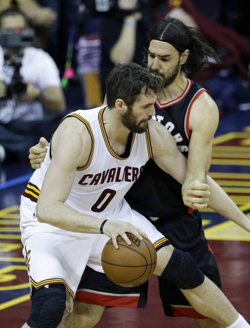 Cleveland Cavaliers' Kevin Love (0) backs down Toronto Raptors' Luis Scola, from Argentina, during the first half of Game 5 of the NBA basketball Eastern Conference finals Wednesday, May 25, 2016, in Cleveland. (AP Photo/Tony Dejak)