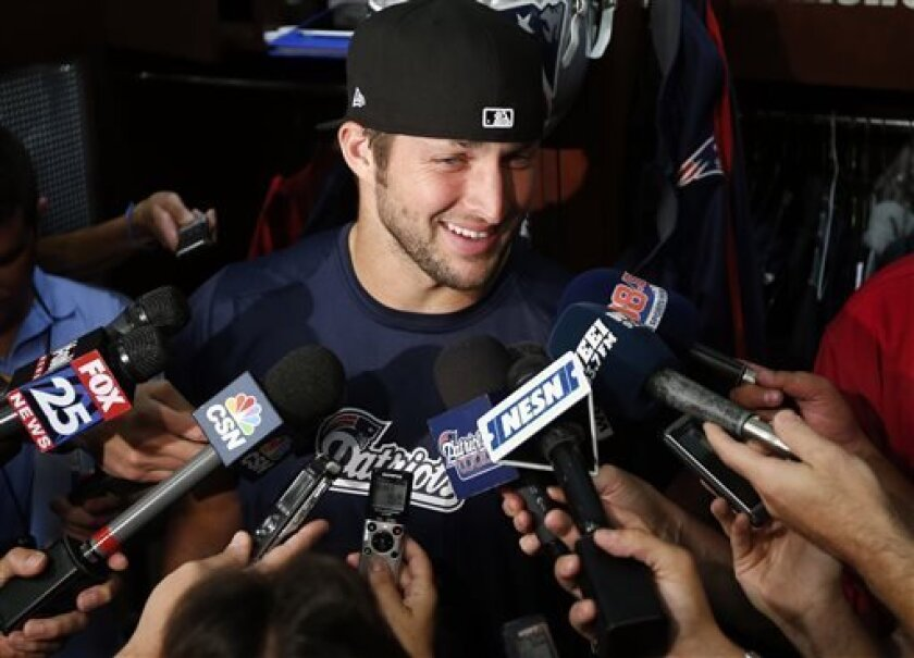New England Patriots quarterback Tim Tebow speaks to media in the locker room after team football practice in Foxborough, Mass., Monday, Aug. 26, 2013. (AP Photo/Elise Amendola)