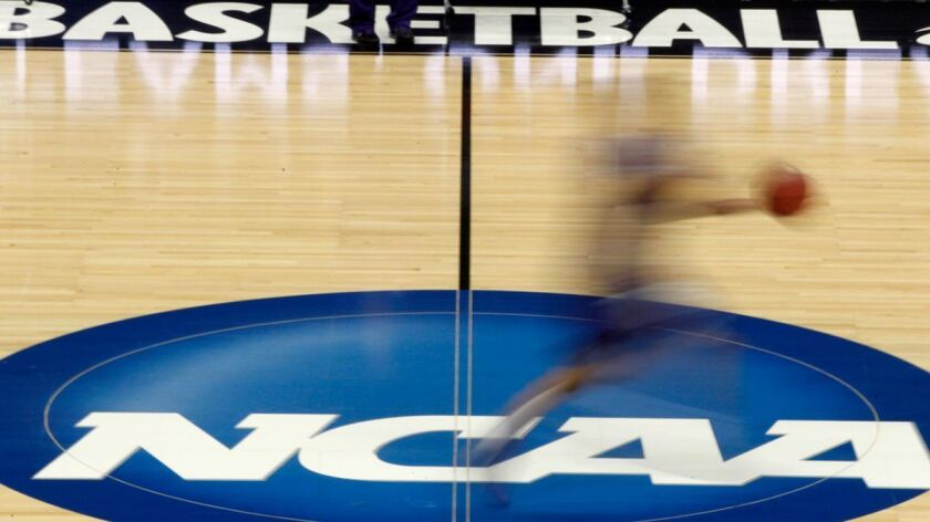A player runs across the NCAA logo during practice in Pittsburgh before an NCAA tournament basketball game in 2012.