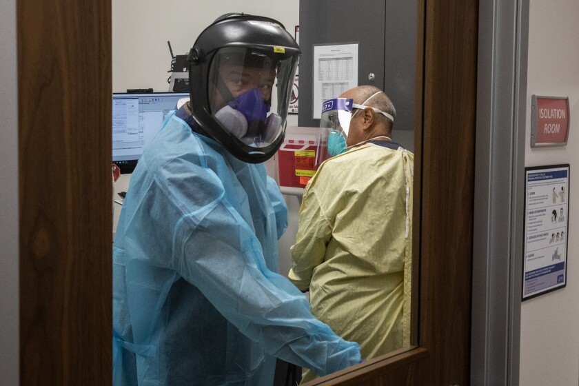 Dr. Juan Manuel Tovar enters an isolation room to tend to a patient at San Ysidro Health Chula Vista Urgent Care Wednesday