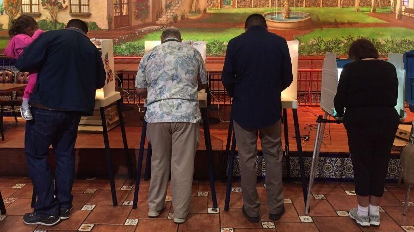 People vote inside the El Mercado de Los Angeles restaurant in the Boyle Heights neighborhood of Los Angeles on November 8, 2016.