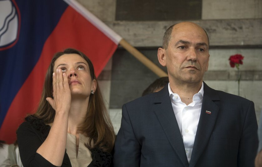 Former Slovenian Prime Minister Janez Jansa, right, stands next to his wife Urska Bacovnik, prior to his departure to prison, in Ljubljana, Slovenia, Friday, June 20, 2014. Jansa has gone to prison to serve a two-year sentence for bribery in an arms deal with a Finnish company. (AP Photo/Matej Lesk