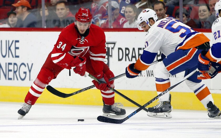 Carolina Hurricanes' Phil Di Giuseppe (34) battles with New York Islanders' Frans Nielsen (51) during the first period of an NHL hockey game, Saturday, Feb. 13, 2016, in Raleigh, N.C. (AP Photo/Karl B DeBlaker)