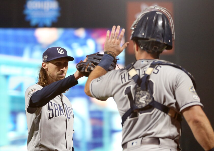 Padres reliever Matt Strahm gets a high-five from catcher Austin Hedges after the eighth inning Thursday against the San Francisco Giants.