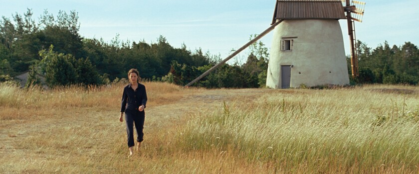 """A woman walks through a field, with a windmill in the background, in the movie """"Bergman Island."""""""