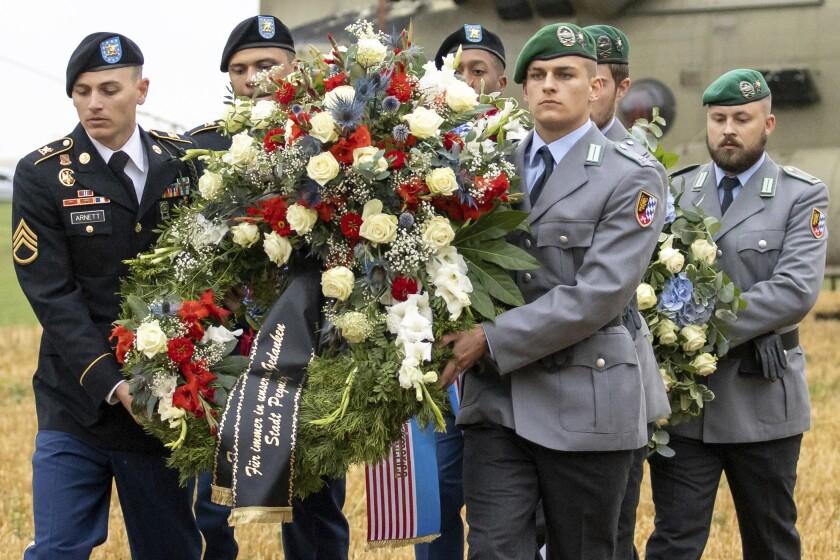 U.S. and German soldiers carry a wreath from a Chinook transport helicopter during a commemoration of a helicopter crash in Pegnitz, Germany, Wednesday, Aug. 18, 2021. On Aug. 18, 1971, a U.S. Army Chinook helicopter crashed near Pegnitz. 37 soldiers were killed. It is the worst accident of the US Army since the Second World War. (Daniel Karmann/dpa via AP)