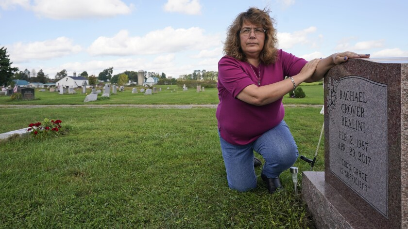Sharon Grover rests her hands on the gravestone for her daughter, Rachael, Tuesday, Sept. 28, 2021, at Fairview Cemetery in Mesopotamia, Ohio. Grover believes her daughter started using prescription painkillers around 2013 but missed any signs of her addiction as her daughter, the oldest of five children, remained distanced. (AP Photo/Tony Dejak)