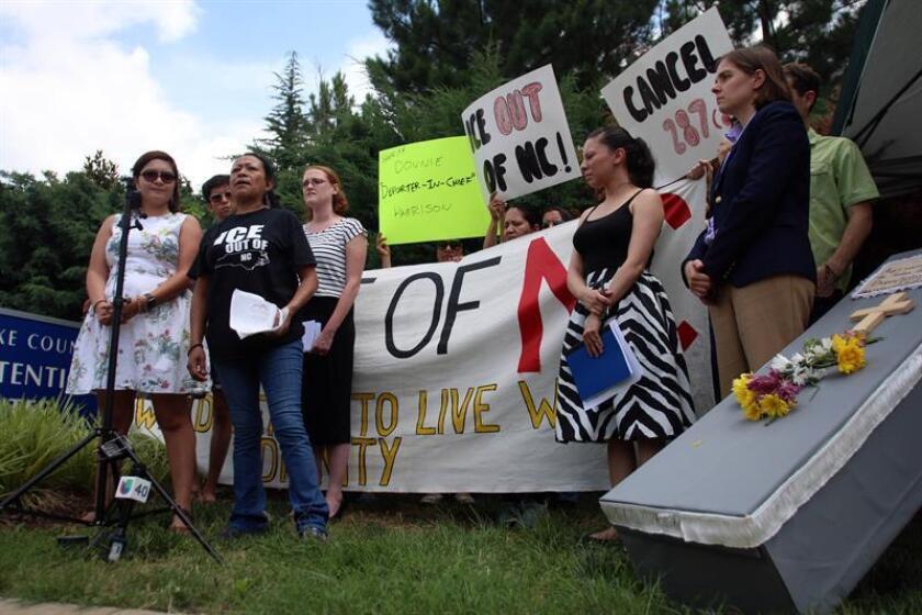 Activistas e inmigrantes sostienen pancartas en contra de la cooperación de la policía con ICE durante una protesta. EFE/Archivo
