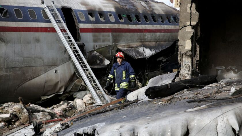 This photo provided by Mizan News Agency, shows an Iranian rescue works at the site of a Boeing 707