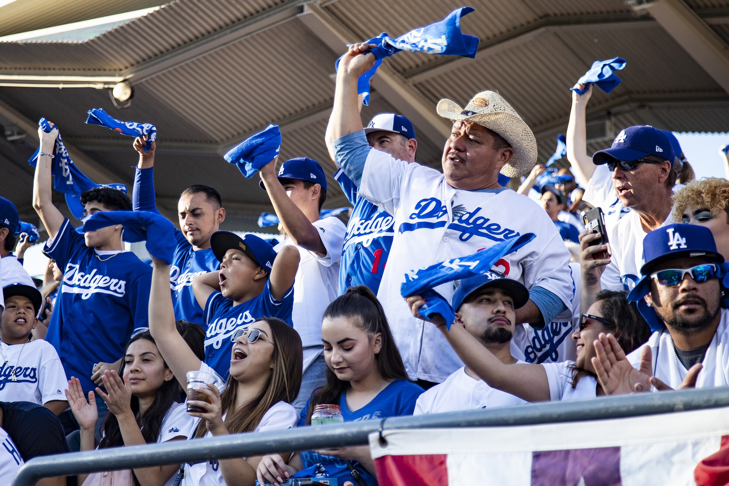 People in Dodgers jerseys stand in the bleachers, yell and wave blue and white bandannas.
