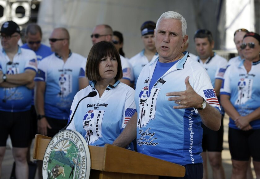 Indiana Gov. Mike Pence speaks as his wife Karen, looks on at the opening ceremony for the Cops Cycling for Survivors fundraising bike ride in Indianapolis, Monday, July 11, 2016. Pence is being considered as a possible running mate for GOP presidential nominee Donald Trump, who is expected to deci