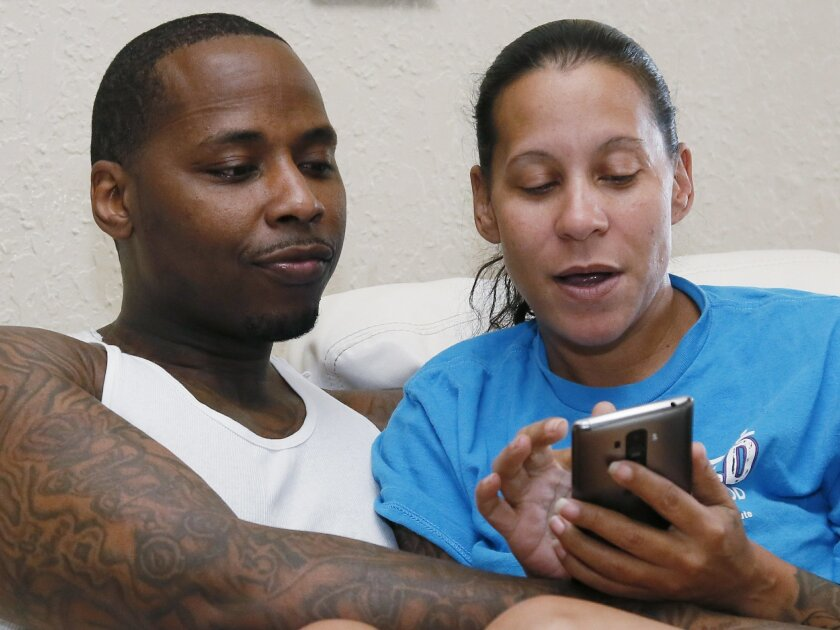 Salaam Moore, left, looks at a page his fiancee, Lola Gaines, right, shows him on her phone at their home in Oklahoma City, Wednesday, July 20, 2016. Moore was convicted of murder in 2001, and sentenced to life in prison without the possibility of parole, but the case was dismissed, all charges vac