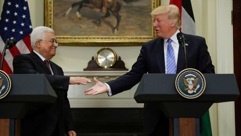 President Donald Trump reaches to shakes hands with Palestinian leader Mahmoud Abbas after speaking