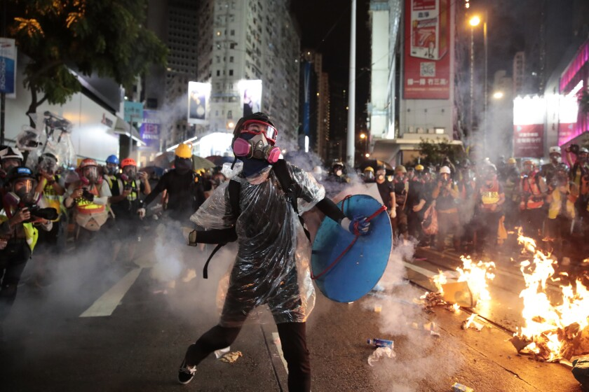 A protester throws a smoking tear gas shell back at police officers in Hong Kong on Saturday.