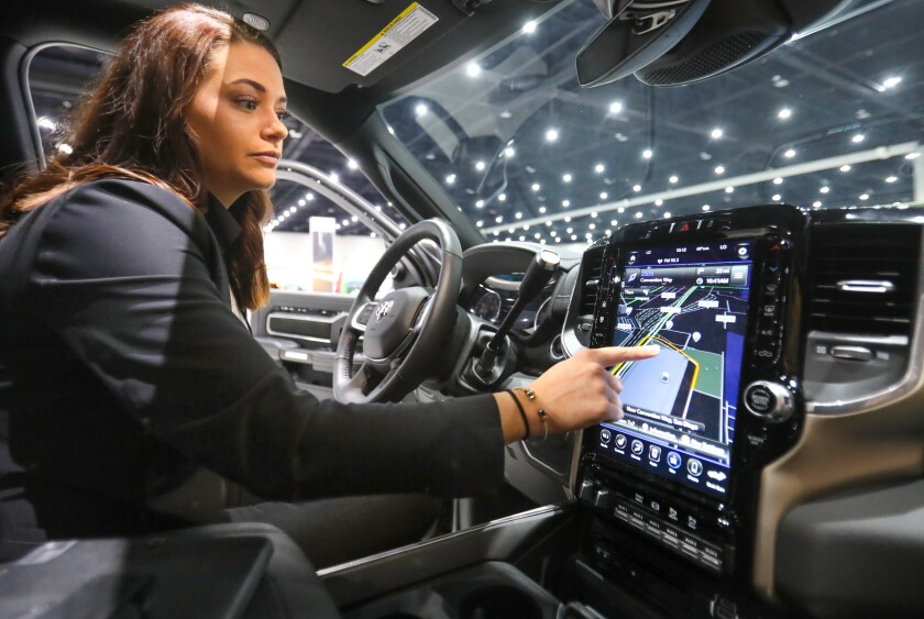 A product specialist for Fiat Chrysler Automobiles demonstrates the 12-inch in-vehicle touchscreen display in a 2019 Ram 2500 Laramie Crew Cab 4x4 pickup truck during the 2020 San Diego International Auto Show Saturday.