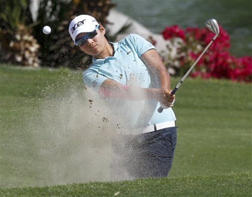 Yani Tseng, of Taiwan, hits from the bunker on the sixth hole during the third round of the LPGA Kraft Nabisco Championship golf tournament in Rancho Mirage, Calif., Saturday, March 31, 2012. (AP Photo/Chris Carlson)