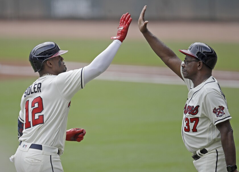 The Braves' Jorge Soler is congratulated by third base coach Ron Washington