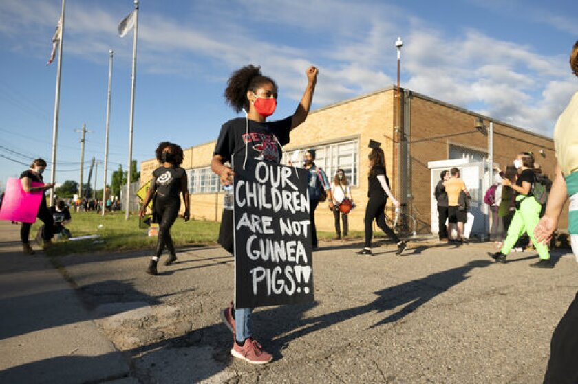 Demonstrators block the driveways of the Detroit Public Schools West Side Bus Terminal to keep school buses from running on the first day of summer school, in Detroit, Monday, July 13, 2020. Concerns about COVID-19 and a lack of safety measures prompted the protesters to demand that schools close. (David Guralnick/The Detroit News)/Detroit News via AP)