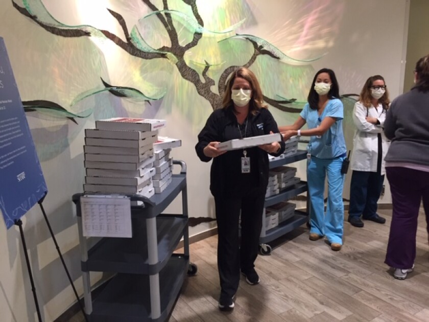Lucinda Camp, nursing administration, distributes pizzas to front-line workers at Sharp Rees-Stealy Del Mar.