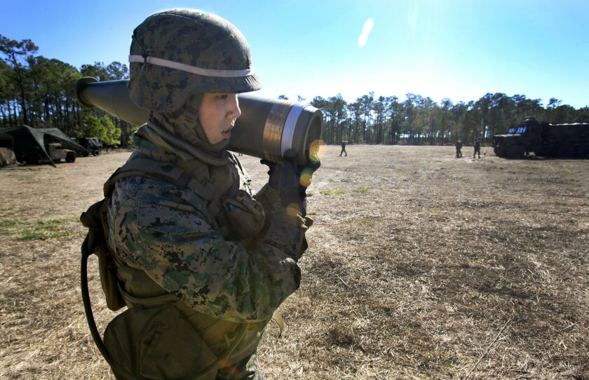 Marine Sgt. Mindy Vuong, a research volunteer in the experimental Ground Combat Element Integrated Task Force based at Camp Lejeune, N.C., carries an artillery shell weighing about 100-pounds.