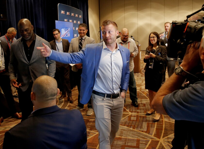 Rams coach Sean McVay, center, and  Chargers coach Anthony Lynn, left, walk through the halls during 2019 NFL meetings.