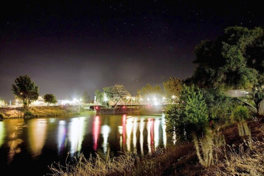 The lights of Walnut Grove illuminate the water along the levees as night falls over the San Joaquin Delta. Slightly more than half of Californians surveyed favored a proposal to replumb the delta — until they learned it would cost $25 billion in ratepayer and government funds. Then only 36% said they would support it.