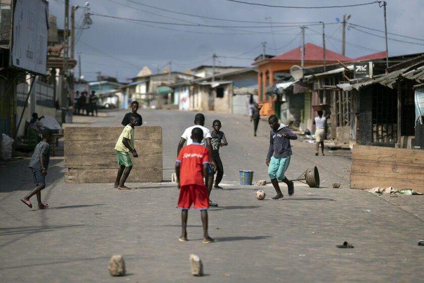 Youth play soccer next to a barricade that was set on a street after protests, earlier this year, against the decision of President Alassane Ouattara's to run for a third term in Bonoua, in the outskirts of Abidjan, Ivory Coast, Friday, Oct. 30, 2020. Opposition activists are threatening to block access to polling stations Saturday in an effort to disrupt the presidential election in Ivory Coast, where incumbent Ouattara is seeking a controversial third term after nearly a decade in power. (AP Photo/Leo Correa)