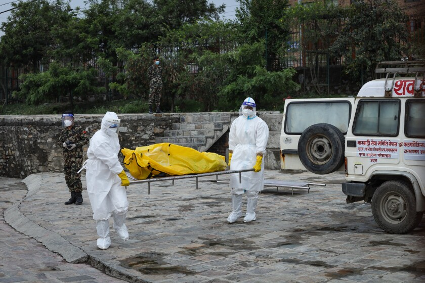 Workers in protective suits carry a body on a stretcher