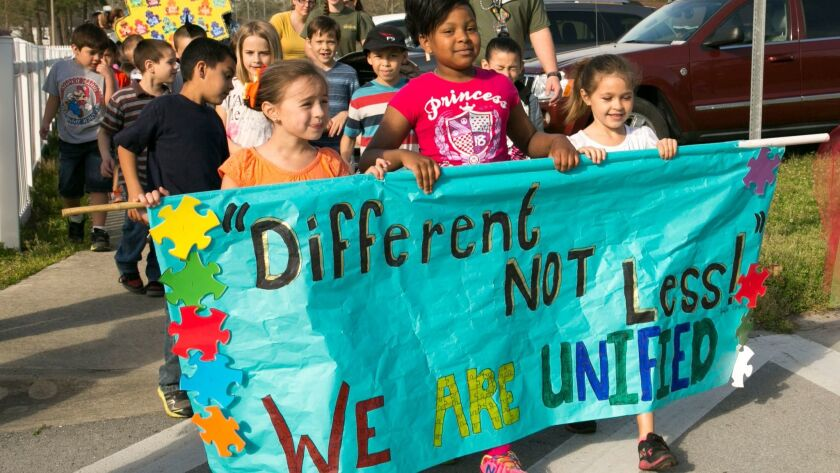 Students and family members from Johnson Primary School march, holding signs and banners in support