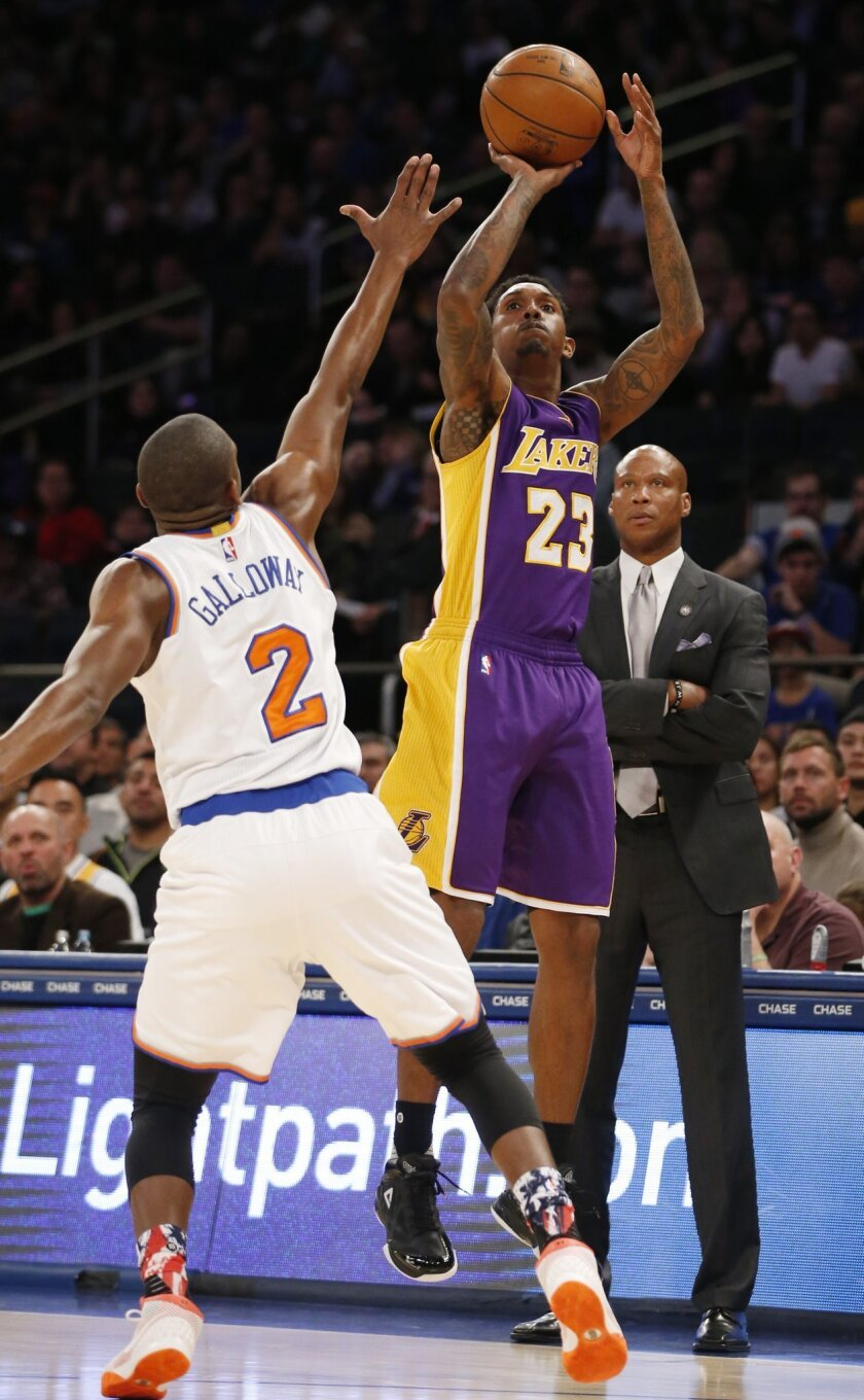 Los Angeles Lakers guard Louis Williams (23) shoots as New York Knicks guard Langston Galloway (2) defends with Lakers head coach Byron Scott watching in the first half of an NBA basketball game at Madison Square Garden in New York, Sunday, Nov. 8, 2015. (AP Photo/Kathy Willens)
