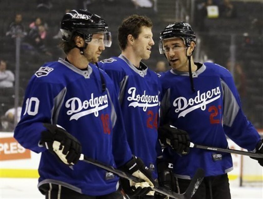 From left, Los Angeles Kings center Mike Richards (10), center Colin Fraser (24) and defenseman Alec Martinez (27) talk during warmups while wearing Los Angeles Dodgers jerseys before an NHL hockey game against the Columbus Blue Jackets in Los Angeles, Thursday, April 18, 2013. (AP Photo/Reed Saxon)