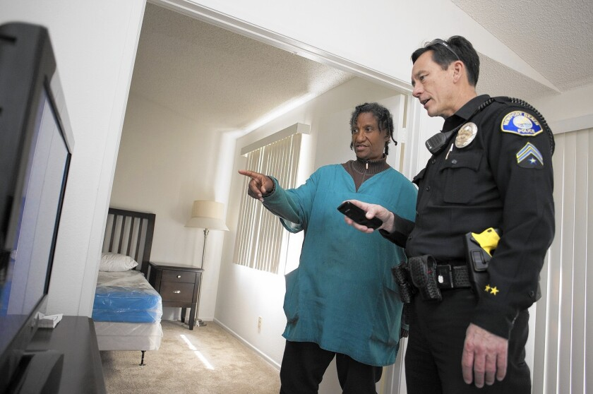 Homeless liaison officer Tony Yim of the Newport Beach Police Department tries to help Toni Horn, 61, get the television working at her new apartment in Lake Forest on Tuesday. Horn spent years on the streets in Newport Beach before getting the apartment with help from Yim.