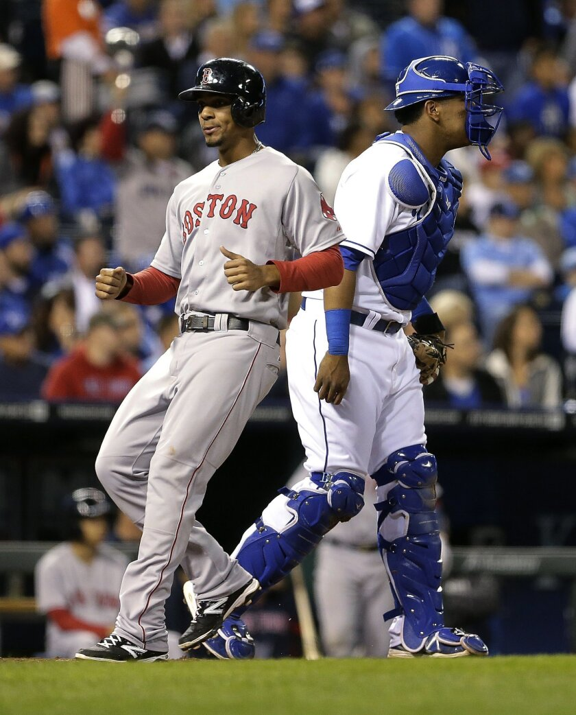 Boston Red Sox's Xander Bogaerts runs home past Kansas City Royals catcher Salvador Perez to score on a single by Will Middlebrooks during the third inning of a baseball game Thursday, Sept. 11, 2014, in Kansas City, Mo. (AP Photo/Charlie Riedel)