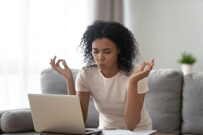 African woman sit on couch near laptop take break reduce stress